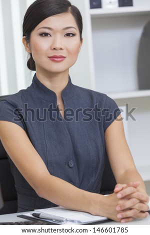 Beautiful young Chinese Asian woman or businesswoman in smart business suit sitting at a desk in an office  - stock photo