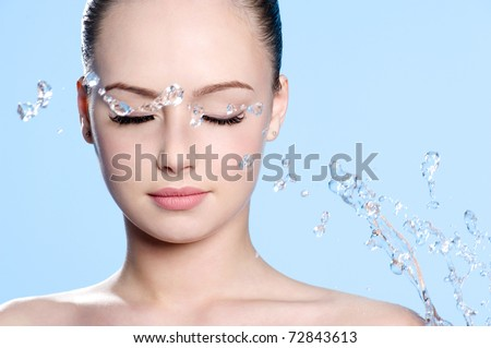 Beautiful young clean female face with splash of water - blue background - stock photo
