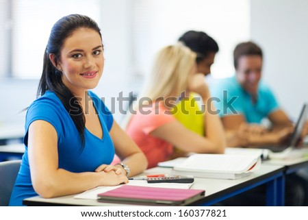 beautiful young college girl in lecture hall looking at the camera