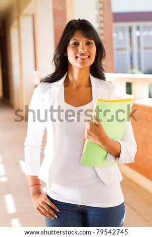 beautiful young college student in school building with books - stock photo