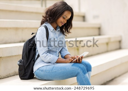 beautiful young college student using smart phone on campus - stock photo