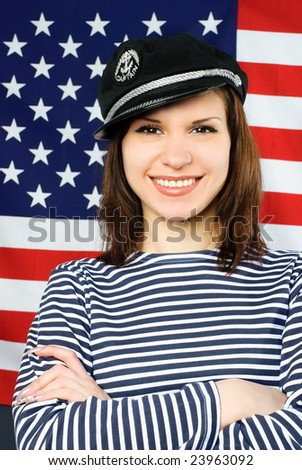 beautiful young confident sailor near the American flag - stock photo