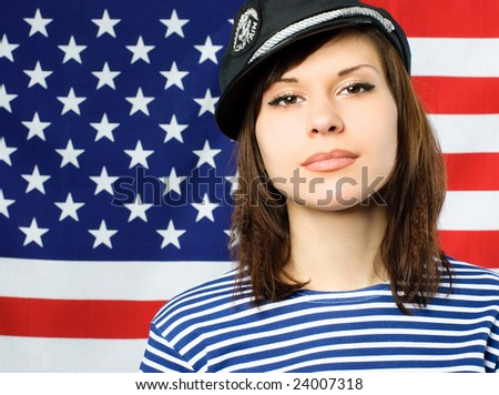 beautiful young confident sailor standing near the American flag - stock photo