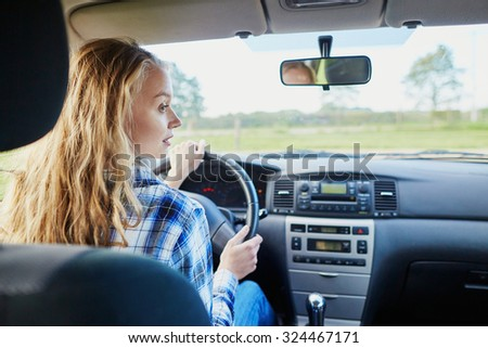 Beautiful young confident woman driving a car - stock photo