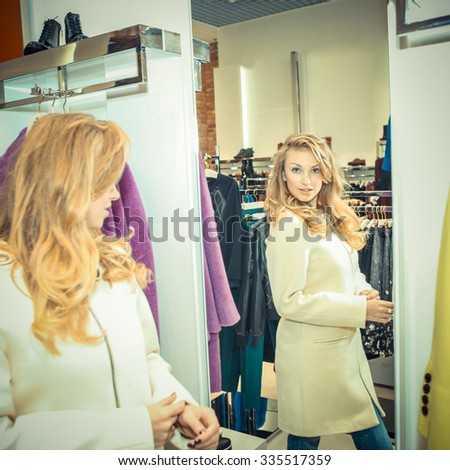 Beautiful young confused woman near rack with clothes. Girl chooses clothes in a boutique
