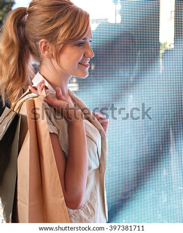Beautiful young consumer woman standing next to a digital led lights screen in a shopping mall carrying paper bags, smiling indoors. Side portrait of attractive woman shopping, lifestyle. - stock photo