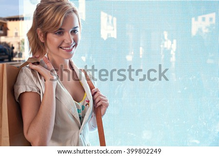 Beautiful young consumer woman standing next to a digital led lights screen in a shopping mall carrying paper bags, smiling indoors. Smiling portrait of attractive woman shopping, lifestyle. - stock photo