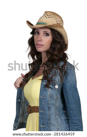Beautiful young country girl woman wearing a stylish cowboy hat - stock photo