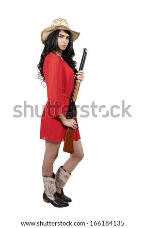Beautiful young country girl woman wearing a stylish cowboy hat shooting a rifle