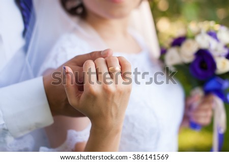 Beautiful young couple a man and a woman. Close-up hand of groom and bride with a wedding ring. Focus on the arm and the ring. bride in white dress. The picture is cropped without faces. - stock photo