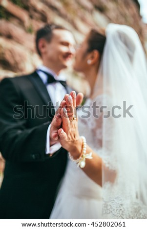Beautiful young couple a man and a woman. Close-up hand of groom and bride with a wedding ring. Focus on the arm and the ring. bride in white dress.  - stock photo