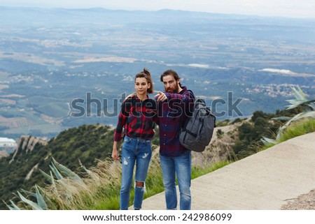 Beautiful young couple admiring the view while out hiking during autumn, backpackers enjoying view standing on mountain trail on high altitude - stock photo