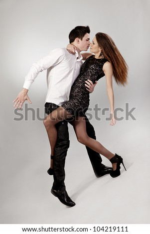 Beautiful young couple are dancing over grey background - stock photo