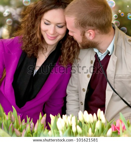 Beautiful young couple buying flowers tulips at the market.