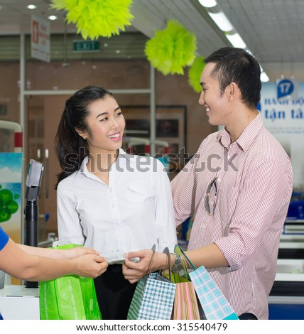 Beautiful young couple buying some clothings at the supermarket and paying with a credit card.
