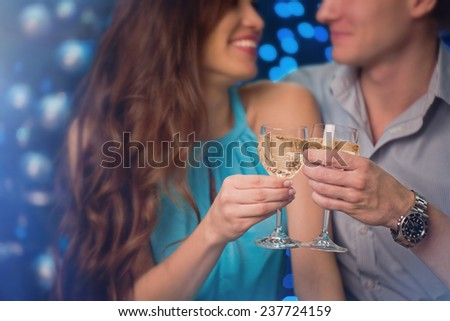 Beautiful young couple celebrating christmas drinking champagne wine - stock photo