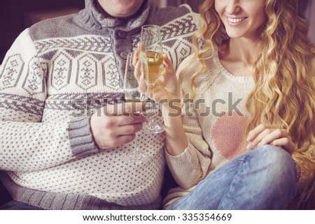 Beautiful young couple celebrating christmas drinking champagne wine. Close up  - stock photo