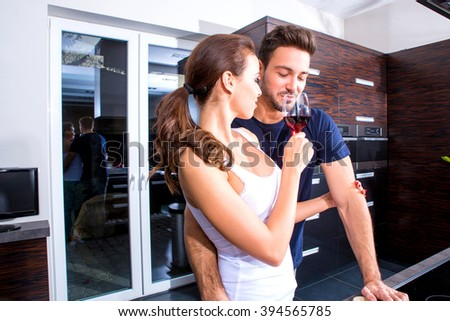 Beautiful young couple cooking while enjoying a glass of wine in the kitchen. - stock photo