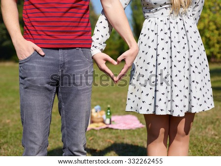 Beautiful Young Couple creating heart with hands, picnic, heart