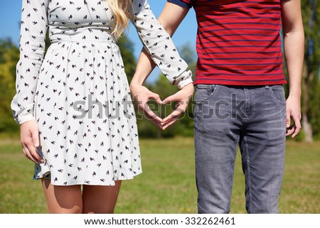 Beautiful Young Couple creating heart with hands, picnic, heart  - stock photo