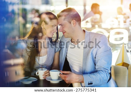 Beautiful young couple drinking coffee in cafe - stock photo