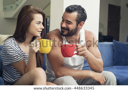 Beautiful young couple drinking coffee in the living room, Couple holding cups of drink and smiling while sitting on sofa at home  - stock photo
