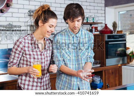 Beautiful young couple drinking orange juice and cooking using flour on the kitchen  - stock photo