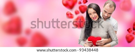 Beautiful young couple embracing and looking at camera. Standing at romantic background, designed in valentine style and ready to use - stock photo
