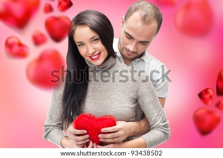 Beautiful young couple embracing and looking at camera. Standing at romantic background, designed in valentine style and ready to use
