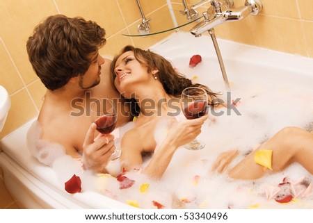 Beautiful young couple enjoying a bath with rose petals - stock photo
