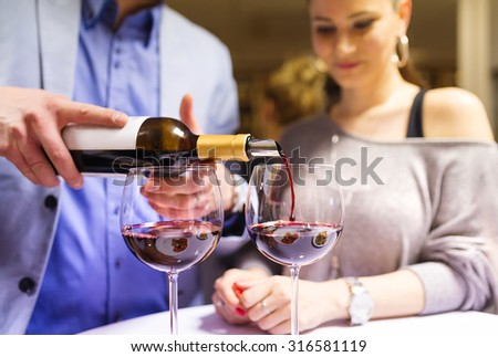 Beautiful young couple enjoying a drink in bar - stock photo