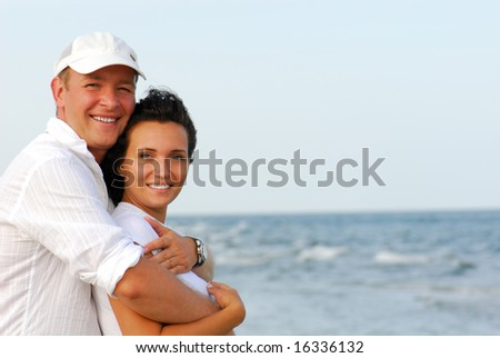 Beautiful young couple enjoying on beach - stock photo