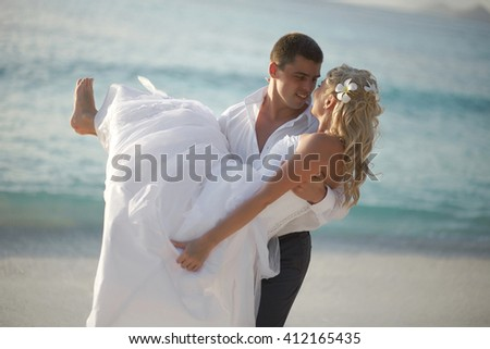 Beautiful young couple enjoying sunset, walking barefoot on beach and playing with each other. Lifestyle wedding on tropical island in caribbean or Hawaii.