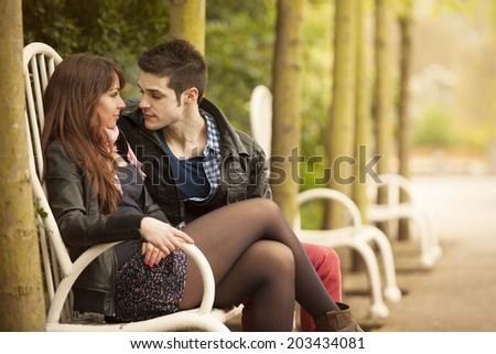 beautiful young couple flirting on bench - stock photo