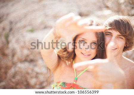 beautiful young couple having fun on the beach frame a picture