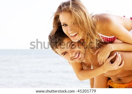 Beautiful young couple having fun on the seaside - stock photo