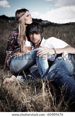 Beautiful young couple hippie posing together over picturesque landscape. - stock photo