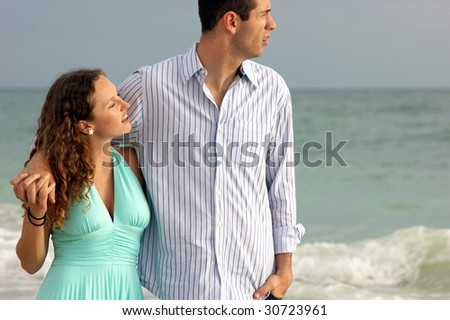 Beautiful young couple holding hands looking out at the gulf of mexico ocean - stock photo