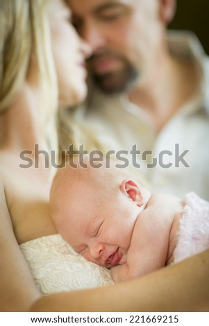 Beautiful Young Couple Holding Their Smiling Newborn Sleeping Baby Girl - stock photo