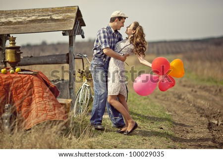 beautiful young couple hugging and kissing in a field near the well and set table with bicycle and colored balloons - stock photo