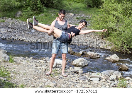 Beautiful young couple hugging in the mountain - stock photo