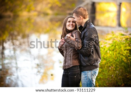 Beautiful young couple hugging near river in park - stock photo