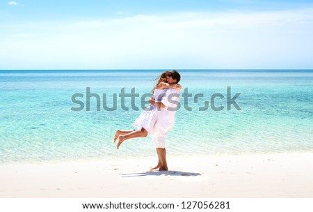 Beautiful young couple hugging on a stunning tropical beach - stock photo