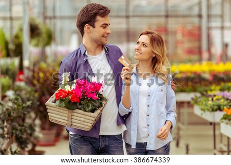 Beautiful young couple in casual clothes is buying plants in orangery with credit card