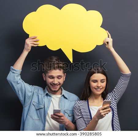 Beautiful young couple in casual clothes is holding a yellow speech bubble, using smartphones and smiling, standing against blackboard - stock photo