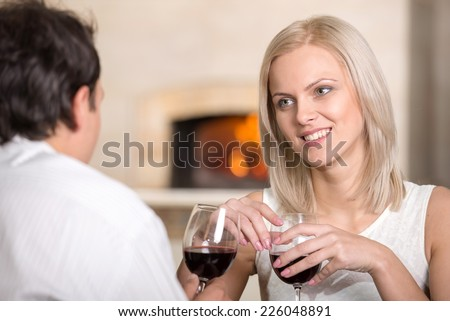 Beautiful young couple in love, couple having fun are talking in cafe and drink wine. - stock photo