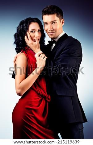 Beautiful young couple in love dancing passionate dance. Studio shot. - stock photo