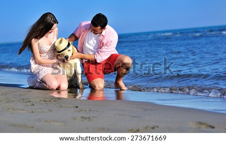 Beautiful young couple in love enjoying and having fun at the beach with their dog