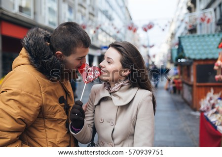 Beautiful young couple in love enjoying together at city street, kissing and holding together a lollipop in heart shape.