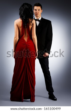 Beautiful young couple in love in evening dresses posing at studio. - stock photo